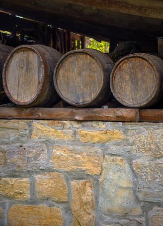 Three old wine barrels on stone wall