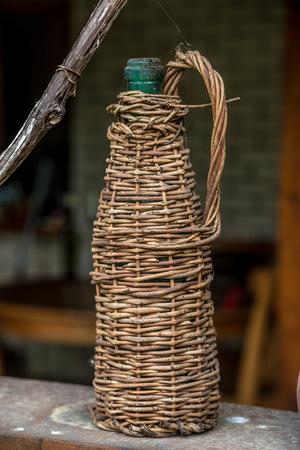 Old wine bottle in wicker packaging