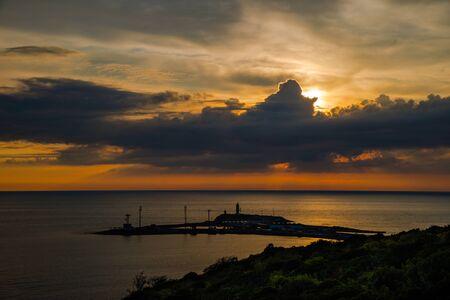 Sunset over the sea and cape of coast Stock Photo
