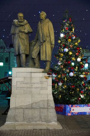 Monument of Stanislavsky and Nemirovich-Danchenko in Chamberlain lane on the Christmas tree background at night, Moscow, Russia