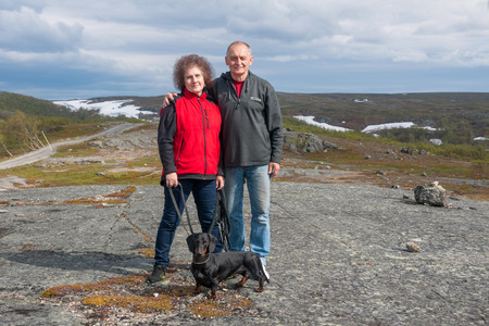 Mature couple with dachshund in mountains in summer, Norway