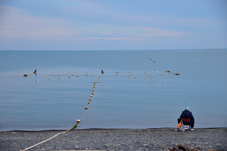 Fisherman is sitting on a pebble beach by sea Stock Photo