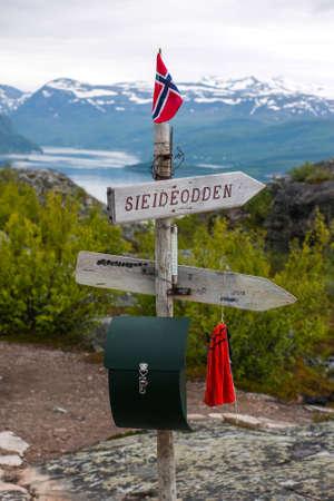 Wooden sign with Norwegian flag on Komsa Mountain - Altas Highpoint towards K?fjord, Norway Stock Photo