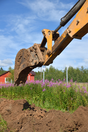 Excavator digging ground on houses and willow-herb background