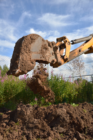 Excavator digging ground on the sky and willow-herb background Stock Photo