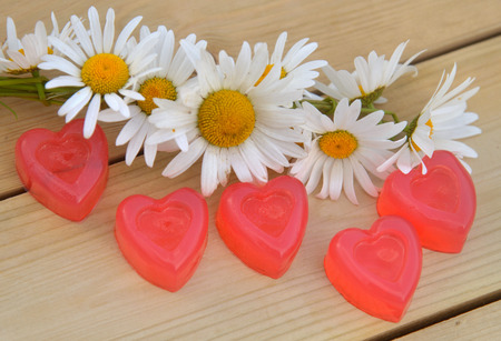 valentines day mother s: Heart of marmalade with a wreath of daisies on wooden boards