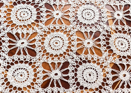Antique white lace on wooden background