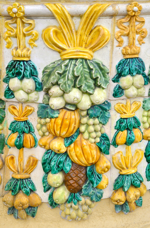 Multi-colored ceramic ornament of flowers, fruits, vegetables, cones, leaves