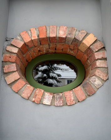 Oval window lined with brick with reflection of winter fir