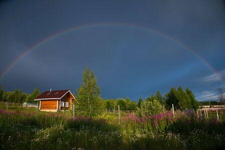 Rainbow over village in summer