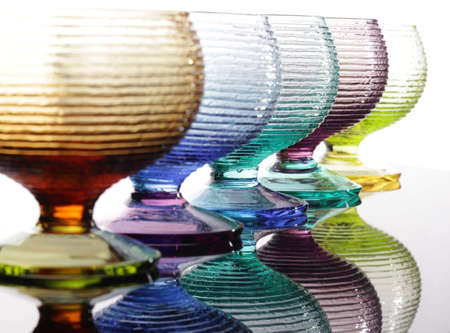 macro film: Five colored glasses with reflection on a table