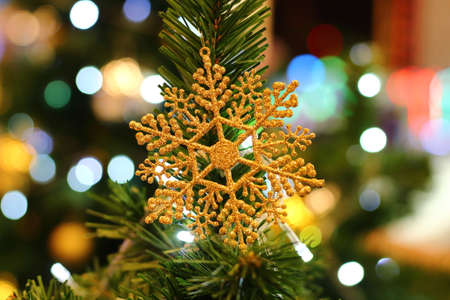 Golden Snowflake hanging on Christmas tree with blur bokeh background.