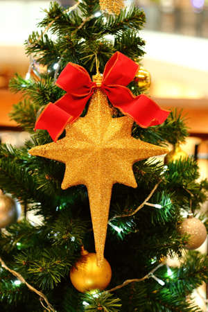 Golden star and red ribbon hanging on Christmas tree.