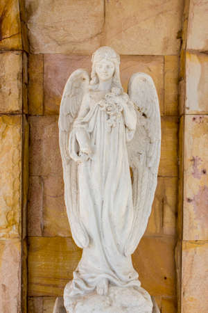 Old white angel statue in the church with stone wall background.