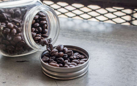 Close up of coffee beans in bottle cap and bottle on concrete floor at the coffee shop with copy space.