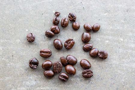 Close up of coffee beans on concrete floor. Top view of brown coffee bean on concrete table.