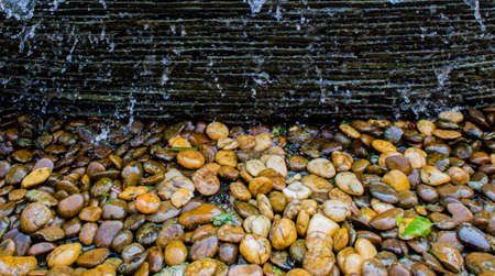 Close up of waterfall on stone wall and colorful pebble on ground in the garden. Stock Photo