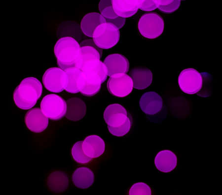 Abstract background of pink bokeh with black background at night.