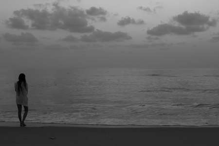 Monochrome of woman standing on the beach at dawn with copy space.