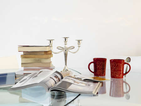 silver plated: pile of books on the crystal table with two red teacup and candlestick made of silver plated
