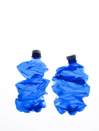 rushed: several rushed blue plastic bottles on the white background