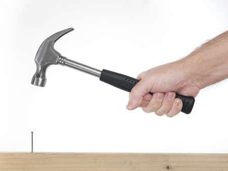 Hand des Menschen, die auf dem weißen Hintergrund während hämmerte Hammer enthalten