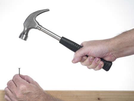 Hand des Mannes, der auf dem weißen Hintergrund während hämmerte Hammer halten