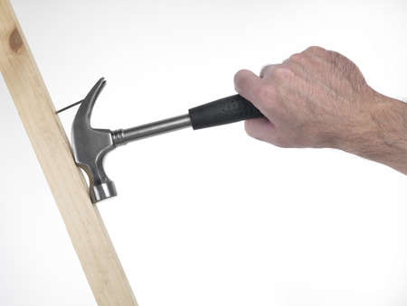 hand of man that hold hammer on the white background during a  extration of nail photo