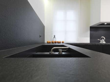 Stahl Wasserhahn für einen schwarzen Marmor Senke für eine moderne Küche Lizenzfreie Bilder