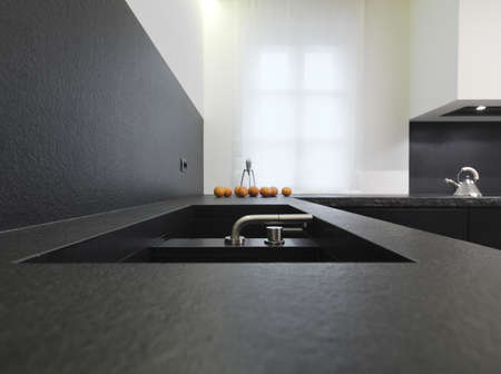 steel faucet for a black marble sink for a modern kitchen