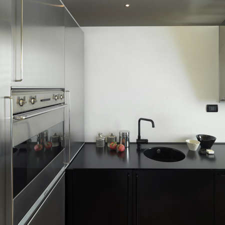 detail of sink in black and steel modern kitchen