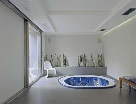 Moderne Badewanne im Keller mit großem Fenster und Blumentopf