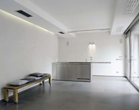 Modern steel kitchen in the basement with white wall and tile floor photo
