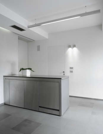 kitchen interior: Modern steel kitchen in the basement with white wall and tile floor