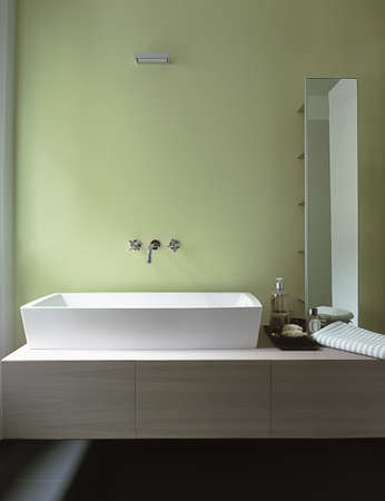washbowl: detail of washbasin in a modern bathroom with green wall Stock Photo