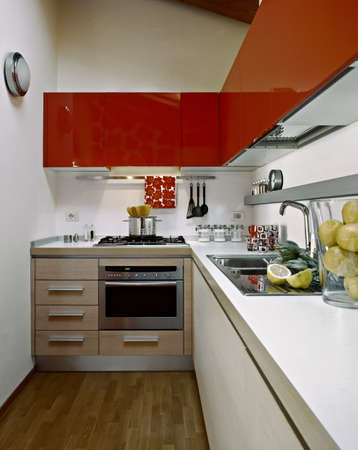 modern kitchen with red cabinets  in a attic room with wood floor photo