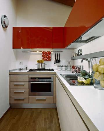 moderne Küche mit roten Schränke in einem Dachzimmer mit Holzboden