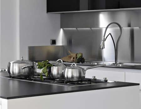 spotřebič: Ocelové pánve na hořáku v moderní kuchyni Reklamní fotografie