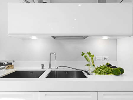 vegetables near the steel sink in a white modern kitchen