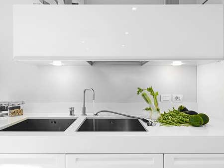 foeniculum vulgare: vegetables near the steel sink in a white modern kitchen
