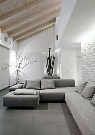 modern gray sofa in the living in a modern attic room Stock Photo