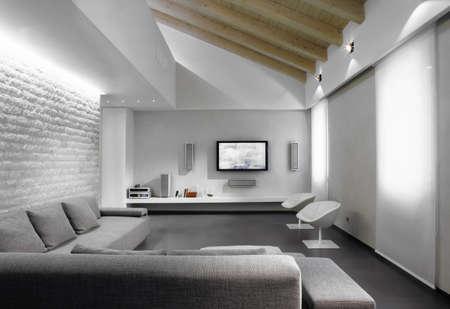 modernen grauen Sofa im Wohnzimmer in einem modernen Zimmer unter dem Dach
