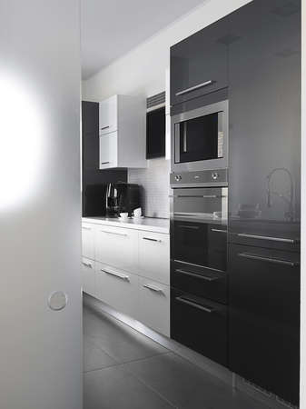 black appliances: modern kitchen with gray tile floor and white wall