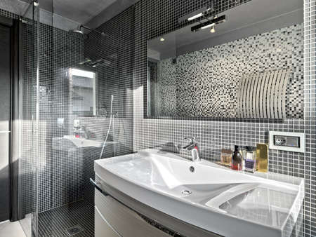 detail of washbasin in a modern bathroom with glass shower cubicle