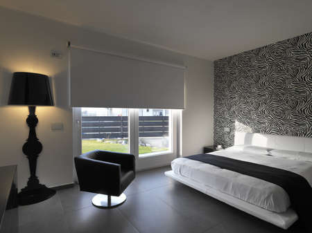 bedding indoors: modern bedroom with leather armchair and black wall lamp