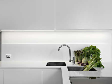 modern white laminate kitchen with vegetables on the white worktop