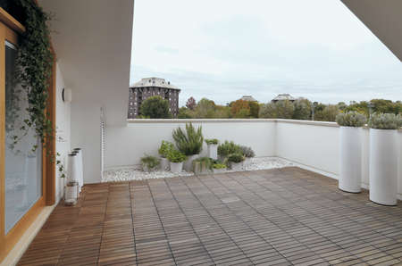 balcony: terrace with wood floor and vase of rasemary Stock Photo
