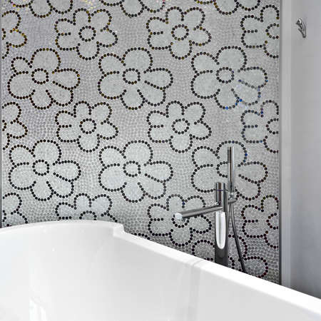 interior desing: detail of bathtub in a modern bathroom with mosaic tile