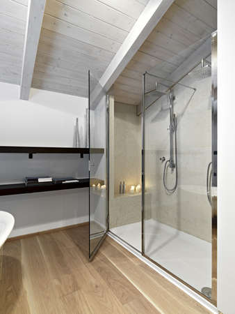 shower cubicle in a modern bathroom on attic with wood ceiling nd parquet Stock Photo