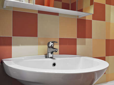 washbasin: steel faucet for a washbasin with colored tiles in a modern bathroom